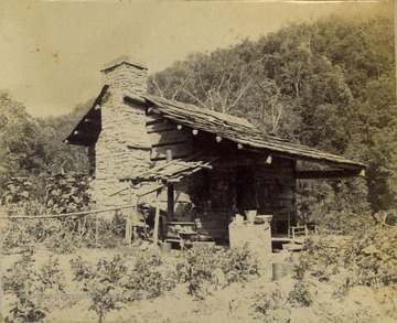A small split-logged cabin with a stone chimney, surrounded by a vegetable garden.