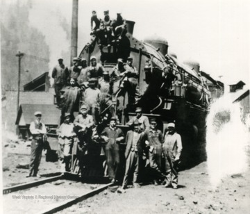 Unidentified railroad workers pose on a locomotive.