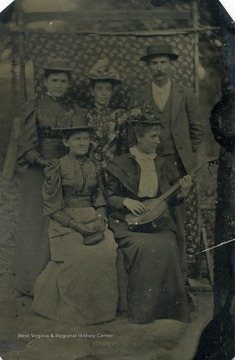 Four unidentified women and one man pose for this tintype as one woman strums a banjo.