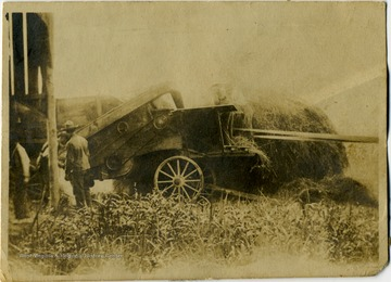 "Information included with the photograph, unidentified workers were ""... probably thrashing clover for seed ... Note the wooden wheels on the thrashing machine."""