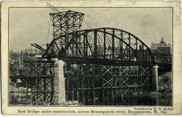 This is a postcard with a photograph on the front of a bridge under construction. The bridge was built across the Monogahela River in Morgantown, West Virginia.