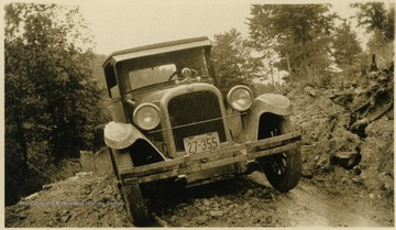 A vehicle on an unpaved road. The vehicle has a West Virginia license plate and is thought to belong to the Mathers/Barrick family.