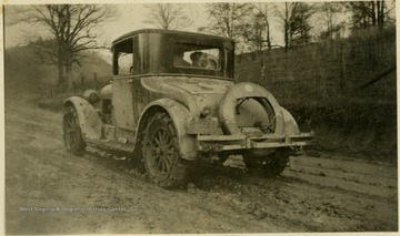 A vehicle with chains on the tires to navigate an unpaved muddy road. It has a West Virginia license plate and is thought to have belonged to the Mathers/Barrick family.