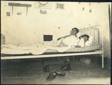Student Leonard Hall awake in bed next to his sleeping roommate in Episcopal Hall Dormitory.