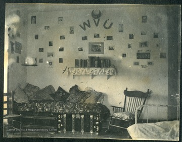 "Room walls decorated with photographs and ""WVU"" . Two steamer trunks covered with a blanket and pillows."
