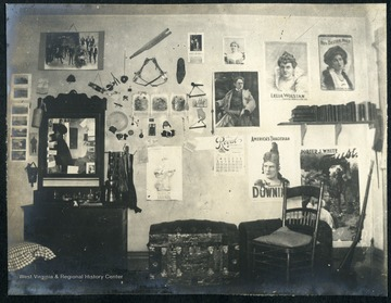 Room furnished with a dresser/wash stand, a trunk and a cadet's rifle in the corner. The walls decorated with posters, calendars, and memorabilia.