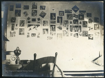 Wall of dorm room covered with photographs.