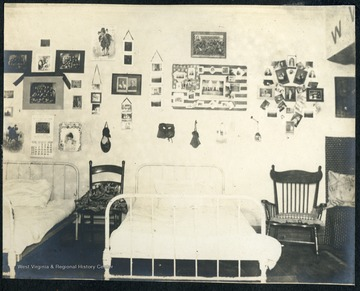 Furnishings include white metal framed beds, a rocker and walls decorated with students' memorabilia and photographs.