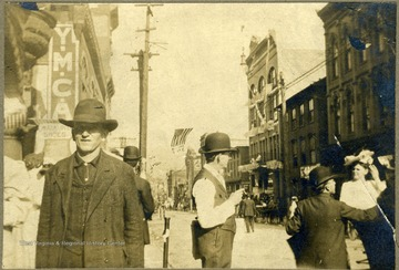 YMCA (Young Men's Christian Association) sign on the left side, behind a man wearing large hat. All persons in the photograph are unidentified.