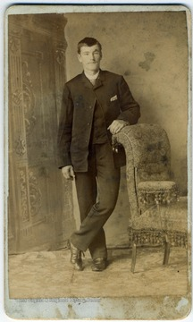 Dressed in the fashion of the late 1800s, posing with his arm resting on a chair.