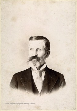 Cabinet card portrait of an older man with a beard wearing a suit and tie.