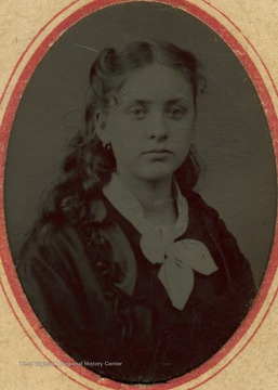 "A young woman identified as Annie B. Baldwin. The name ""William A. Gatentin"" is written on the back of the image."