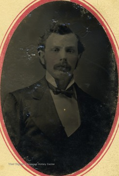 A young man with a mustache,dressed in a suit and bow tie.