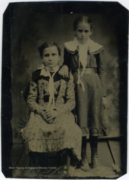 Two young girls (probably 8 or 9 years old). They both have their hair pinned back and are wearing long dresses below the knee dresses in the fashion of the day for children.