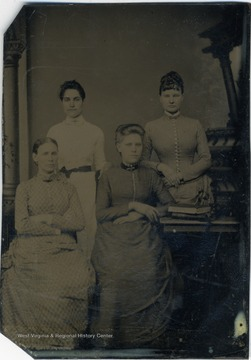 Four young women all wearing long, high collared dresses.