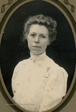 A young woman in a high neck white dress. She appears to be wearing both a necklace and a pin watch.