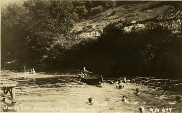 Postcard photograph of of several swimmers and one boy paddling a canoe. All persons in the photograph are not identified.