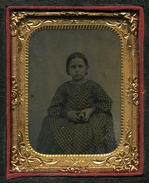 Probably a tintype photograph of a unidentified girl wearing mid-19th style dress and hair, holding an object.