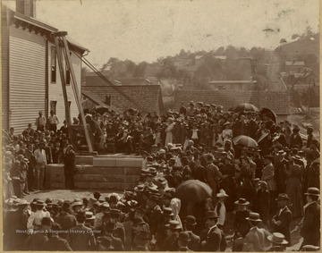 Large crowd gathered around the pulley to set the stone. No one is identified.