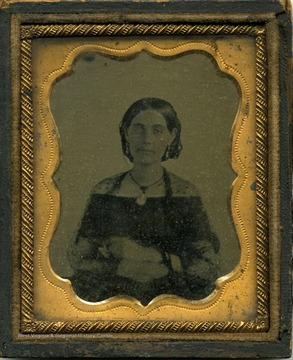 Possibly a tintype of a young woman wearing the style of dress and hair for the Civil War era.