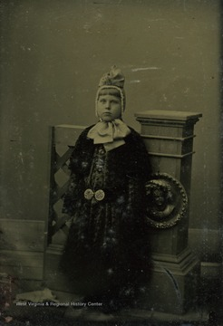 Unidentified young girl poses wearing a large outer garment, held at the waist with ornat belt, and a bonnet tied with a huge ribbon.