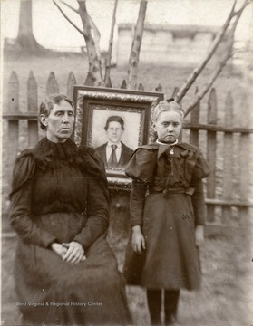 Flota Maud Bomer (Huffman) was the child of Sarah E. Summers Wolfe and William Bomer. The portrait in the photograph is Elijah Summers died in the battle of Cross Keys during the Civil War from sunstroke.