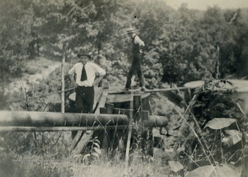 Fred S. Hathaway and unknown person walking oil pipeline.