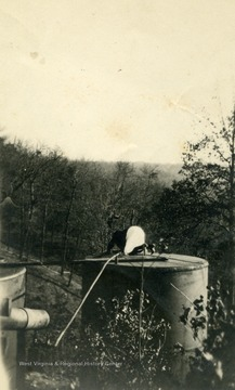 Unknown person kneeling on top of an oil well.