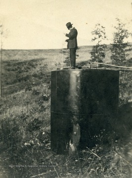 Fred S. Hathaway on top of an oil tank loacted on Dr. W. T. W. Dye's farm.