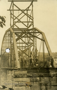 Unidentified workmen stand on stone piers during construction on the Grantsville Bridge.