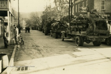 Trucks loaded with scrap metal, driving through town. Many citizens pitched in to support the war effort by collecting materials for recycling.