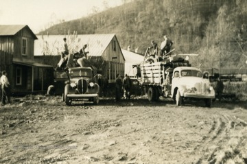 "Collecting scrap metal in the back of trucks. Calhoun County citizens aided the war effort by collecting scrap metal to be receycled into miltary needs. The John Deer Company encouraged farmers to ""Sink a sub from your farm, bring in your scrap metal""."