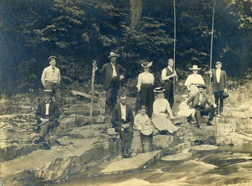 Only identified member of the fishing party is Eva Dye Hathaway- young woman sitting center front wearing a hat.