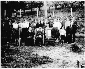 "Information included with the photograph: ""Taken after Billy Burn's funeral.[ The Rev. Burns, originally from Kentucky was reportedly involved in stopping the feud between the Hatfields and the McCoys.] Identified Front Row L to R: Aunt ""Polly"" Johnson, Florinda Stump Burns, a picture of Rev. Billy Burns, Glen Weaver; Back Row: Scott Burns, Della Burns, either a Johnson or Stewart girl, Stella Burns, Everett Burns, Harper Burns, Arlan Burns (in front of Harper), Minnie Burns, Jennie Burns, Charlie Burch, Claud Osborn, Dell Burns, Rose Burns Moore, Elma Burns (baby), Rachel Gherke Burns, Calvin Burns, John Burns, Emma Burns, Frank Weaver."""