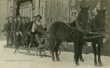 "Seated on the sled are: Charles Marshall, Hugh Ferrell, Dallas Stutler, Bill Hamilton, Orda Chenoweth, Ray Blizzard, Harry Smith, and ""Budge"" Marshall, driving."