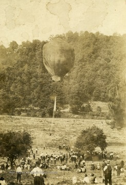 People watch as a man goes up in a hot air balloon.