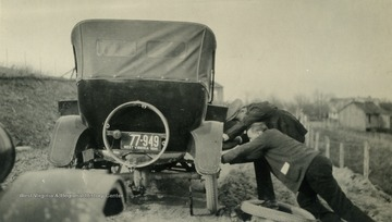 Two men change a tire on a Model T Ford.