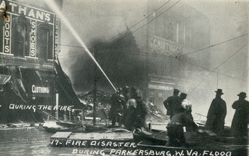 Firemen attempt to control the fire at Nathan's Clothing Store from a boat.