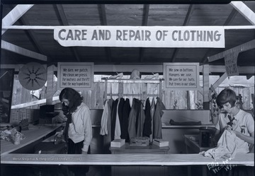 Two 4-H members demonstrate proper clothing care.