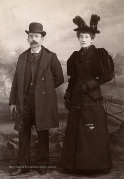 A cabinet card photograph of a couple waering the fashions of the day including hats.