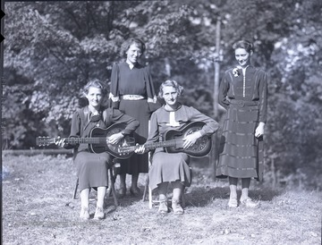 Group portrait of four unidentified 4-H members, two with instruments.