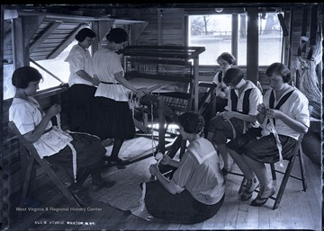 Campers use a loom to weave cloth.