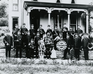 "Members identified, back row L to R: ? , Bert Johnson, ? , John Robert Martin, Harry Johnson, Tommy Burke, ___ Collins, Frank Wells, Bill Wells. Front row L to R: ? , Jeff Collins, Bill Morris, Clark Johnson, Lot Thomas, (little girl)Isabelle Thomas, Morris Clovis, Will Howard, Oz Wade. Young boy in front next to Lot Thomas is Ross Collins. Also inscribed on the back : ""Lot Thomas furnished the uniforms for the band. Suits were red with gold braids. Mae Johnson Howard made Mr. Thomas' uniform  The men took up a collection and presented it to Lot. Picture taken in front of Lot Thomas home. This home is now the Robert Ownen Funeral Home. At one time this band played for John Phillip Sousa."" Labeled on back: ""Sara Scott"""