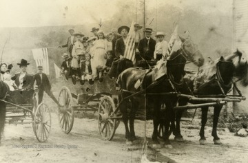 "Identified; far left-center, ""Aunt"" Mae Howard (in the buggy holding a baby); in the back of the wagon, standing sixth from right, Jessie Chaplin; Standing in the front-center of the wagon, Will Howard. Inscribed on the photograph, ""The photograph was taken at the foot of the town hill in front of the old building built for the Baptist Church and upstairs Odd Fellow Lodge."" Labeled on back: Sara Scott"