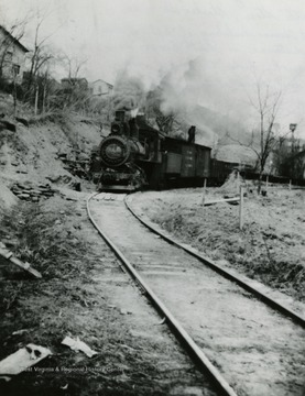 M & W Railway coming around the bend at Scotts Store in Blacksville, West Virginia. Lott Thomas building at left on bank. In distance is Smith Brocks barn and wash house. The smoke hides the Brock home. The bird house at the right is the back of the Thomas property. Photo labeled: Sara Scott