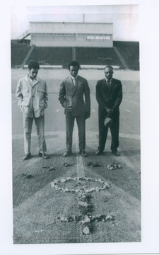 Two Marshall football players, who were injured and didn't fly with the team on a plane which crashed and killed all 75 aboard, visit a symbolic wreath of flowers on Marshall's football field with the father of one of the victims. From left: Felix Jordan, Cincinnati, OH.; Nat Ruffin, Quincy, Fla.; and Lucian Sanders, Tuscaloosa, Ala., father of football player Larry Sanders.