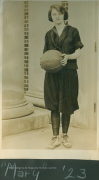 "Player identified as ""Mary"" poses in uniform holding a basketball."