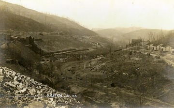 Railroad tracks run down the middle of the valley, while cleared mountainsides give way to industrial operations pictured on the left and the town buildings on the right.