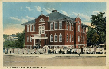Students lined up outside of red brick school building. See original for correspondence. Published by Louis Kaufmann & Sons. (From postcard collection legacy system.)