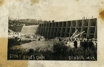 People visit the Stony River Dam, observing from the top and bottom. (From postcard collection legacy system.)